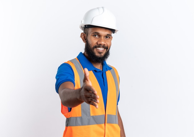 Glimlachende jonge afro-amerikaanse bouwer man in uniform met veiligheidshelm stak zijn hand uit geïsoleerd op een witte achtergrond met kopie ruimte