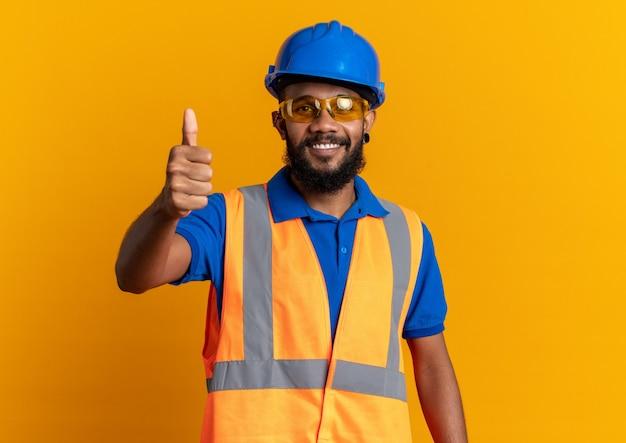 Glimlachende jonge afro-amerikaanse bouwer man in veiligheidsbril dragen uniform met veiligheidshelm duimen omhoog geïsoleerd op oranje achtergrond met kopie ruimte