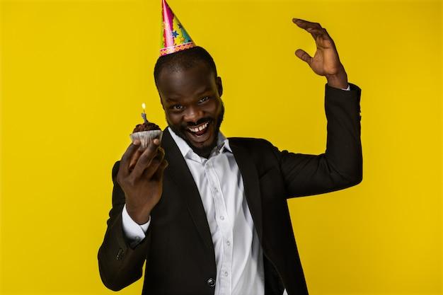 Glimlachende jonge afro-amerikaanse kerel in zwart kostuum en verjaardagshoed met brandende kaars