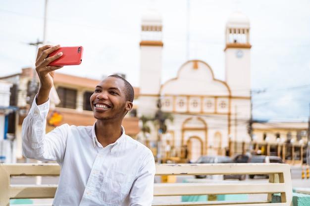 Glimlachende jonge afro-amerikaanse man die een selfie maakt met een moskee erachter
