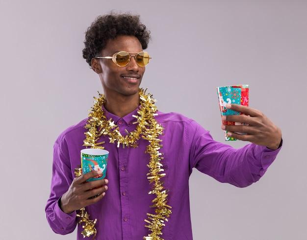 Glimlachende jonge afro-amerikaanse man met bril met klatergoud slinger rond de nek houden van plastic kerstbekers uitrekken en kijken ernaar geïsoleerd op witte achtergrond