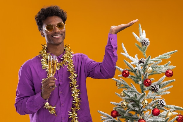 Glimlachende jonge afro-amerikaanse man met bril met klatergoud slinger rond de nek staande in de buurt van versierde kerstboom met glas champagne