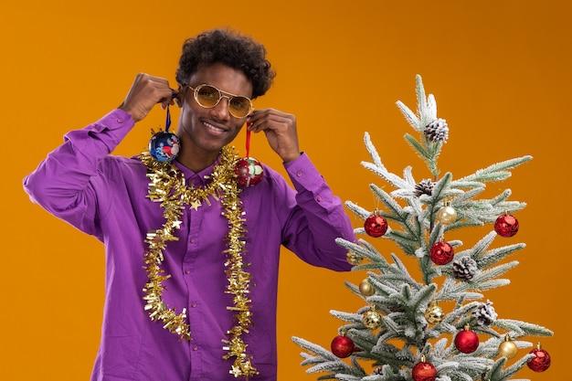 Glimlachende jonge afro-amerikaanse man met bril met klatergoud slinger rond de nek staande in de buurt van versierde kerstboom opknoping kerstballen op oren geïsoleerd op oranje muur