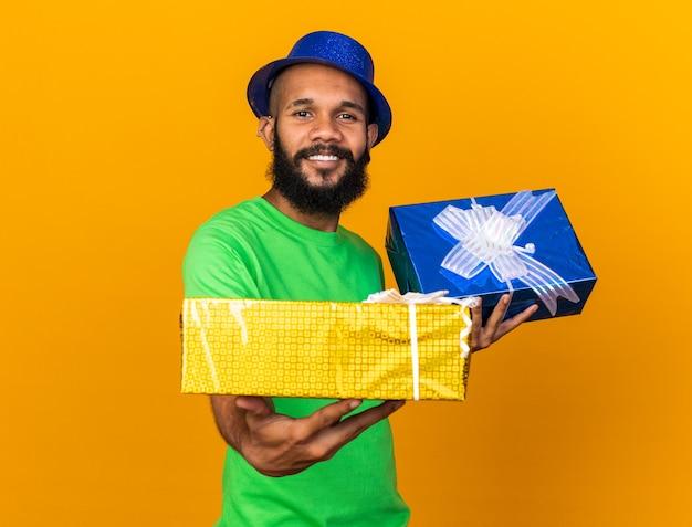 Glimlachende jonge afro-amerikaanse man met een feesthoed die geschenkdozen aan de voorkant vasthoudt, geïsoleerd op een oranje muur