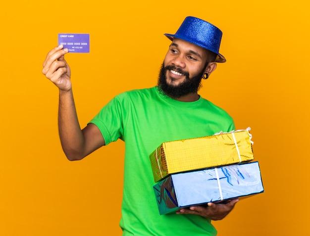 Glimlachende jonge afro-amerikaanse man met een feesthoed die geschenkdozen vasthoudt en naar een creditcard kijkt die op een oranje muur is geïsoleerd