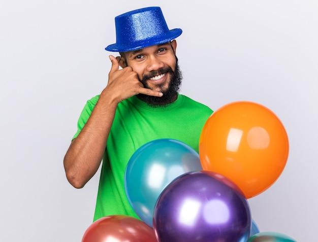 Glimlachende jonge afro-amerikaanse man met een feestmuts die achter ballonnen staat en een gebaar van een telefoongesprek laat zien