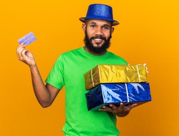 Glimlachende jonge afro-amerikaanse man met een feestmuts met geschenkdozen met creditcard