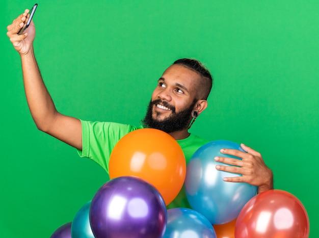 Glimlachende jonge afro-amerikaanse man met een groen t-shirt achter ballonnen, neemt een selfie