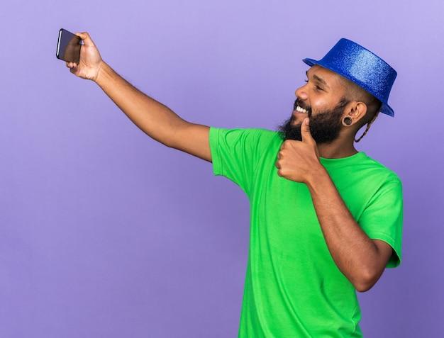 Glimlachende jonge afro-amerikaanse man met feesthoed neemt een selfie met duim omhoog geïsoleerd op blauwe muur