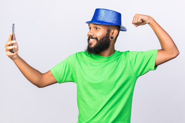 Glimlachende jonge afro-amerikaanse man met feesthoed neemt een selfie met een sterk gebaar
