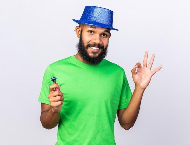 Glimlachende jonge afro-amerikaanse man met feestmuts die een goed gebaar toont met feestfluitje