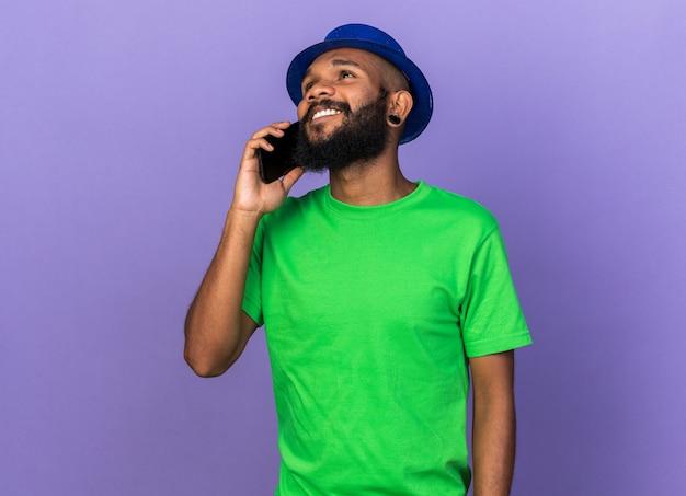 Glimlachende jonge afro-amerikaanse man met feestmuts spreekt aan de telefoon
