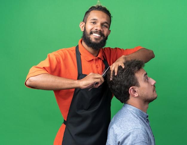 Glimlachende jonge afro-amerikaanse mannelijke kapper die uniform draagt en kapsel doet voor zijn jonge klant