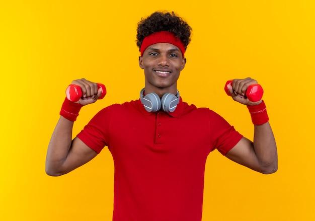 Glimlachende jonge afro-amerikaanse sportieve man met hoofdband en polsband in koptelefoon op nek verhogen halters geïsoleerd op gele muur