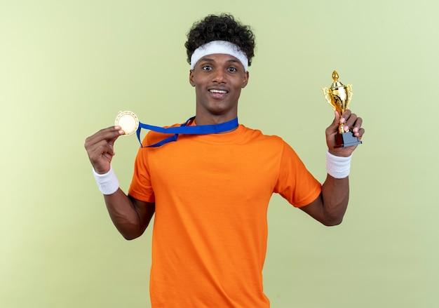 Glimlachende jonge afro-amerikaanse sportieve man met hoofdband en polsbandje met de beker van de medailleholding geïsoleerd op groene achtergrond
