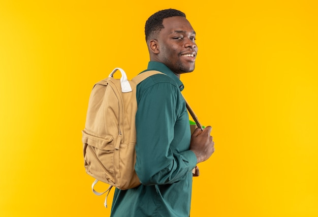 Glimlachende jonge afro-amerikaanse student met rugzak staande, zijaanzicht