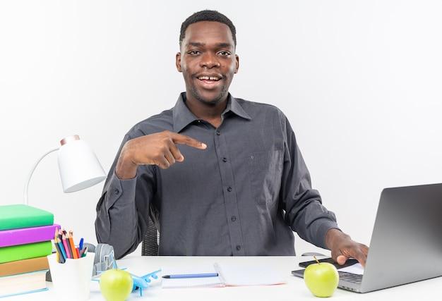 Glimlachende jonge afro-amerikaanse student zit aan bureau met schoolhulpmiddelen wijzend op laptop