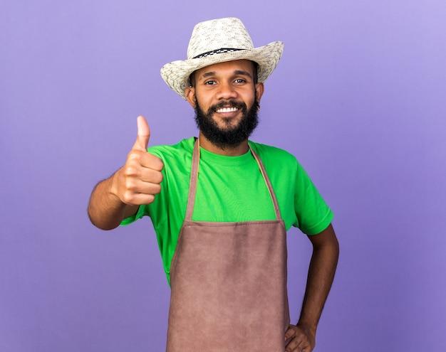 Glimlachende jonge afro-amerikaanse tuinman die een tuinhoed draagt die zijn duim laat zien