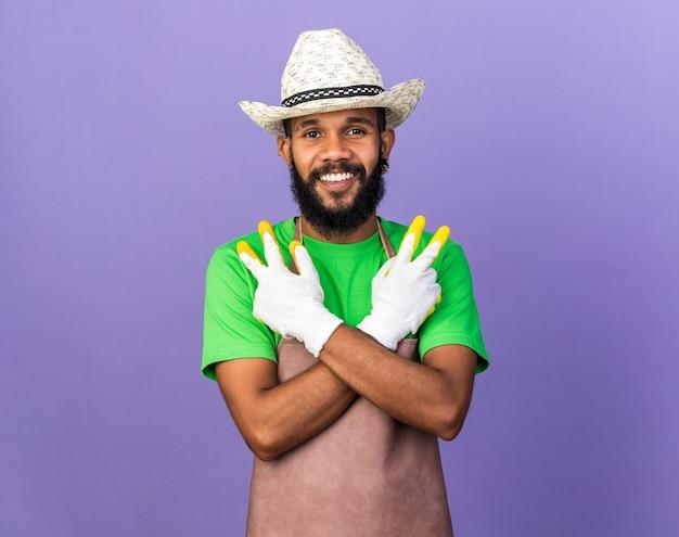 Glimlachende jonge afro-amerikaanse tuinman die een tuinhoed draagt met handschoenen die een vredesgebaar tonen dat op een blauwe muur is geïsoleerd