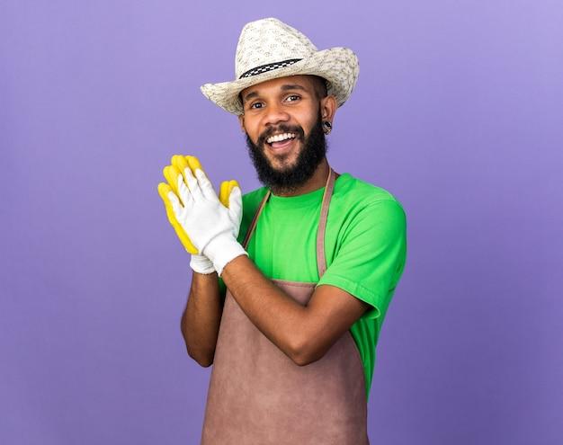Glimlachende jonge afro-amerikaanse tuinman die een tuinhoed draagt met handschoenen die elkaars hand vasthouden