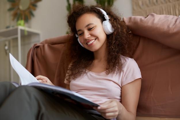 Glimlachende jonge afro-amerikaanse vrouw met krullend haar zitten in de kamer, gekleed in pyjama's, genieten van zijn favoriete muziek in de koptelefoon, een nieuw tijdschrift lezen, glimlachen en genieten van de zondag.