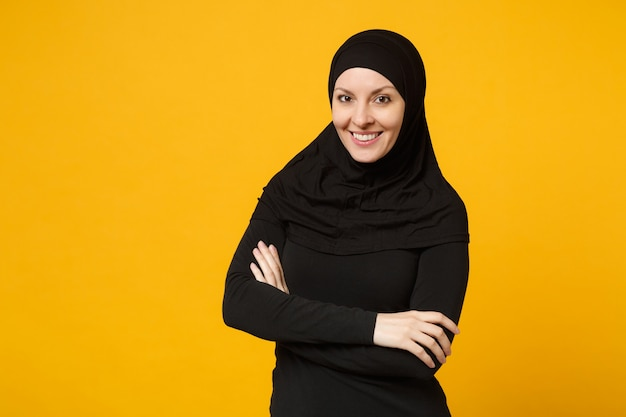 Glimlachende jonge arabische moslimvrouw in hijab zwarte kleding houdt handen gevouwen, geïsoleerd op gele muur, portret. mensen religieuze levensstijl concept.
