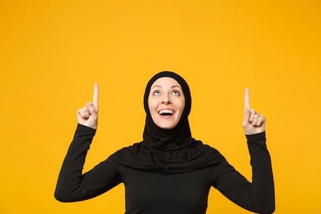 Glimlachende jonge arabische moslimvrouw in hijab zwarte kleding met wijzende kopie ruimte met handen vinger geïsoleerd op gele muur portret. mensen religieuze levensstijl concept.