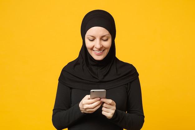 Glimlachende jonge arabische moslimvrouw in hijab zwarte kleren houden in handen mobiele telefoon, chatten geïsoleerd op gele muur portret. mensen religieuze levensstijl concept. .