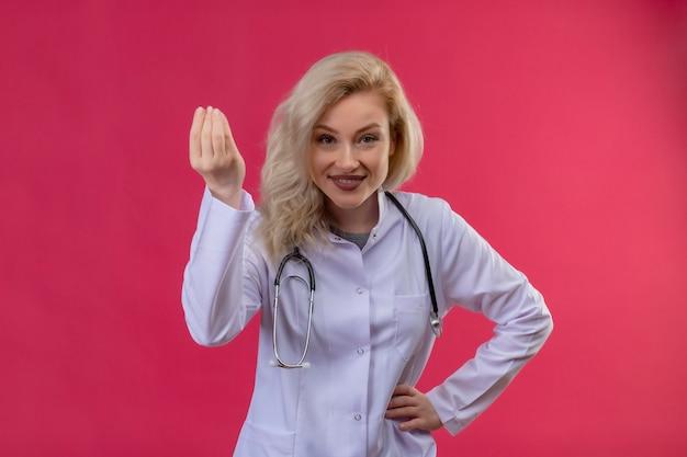 Glimlachende jonge arts die stethoscoop in medische toga draagt die contant geldgebaar op rode backgroung toont