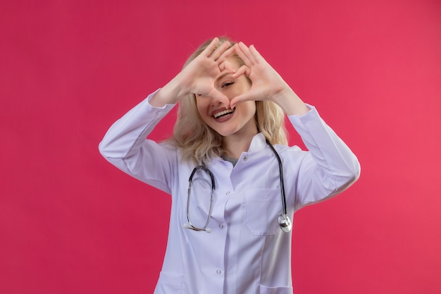 Glimlachende jonge arts die stethoscoop in medische toga draagt die hartgebaar op rode backgroung toont