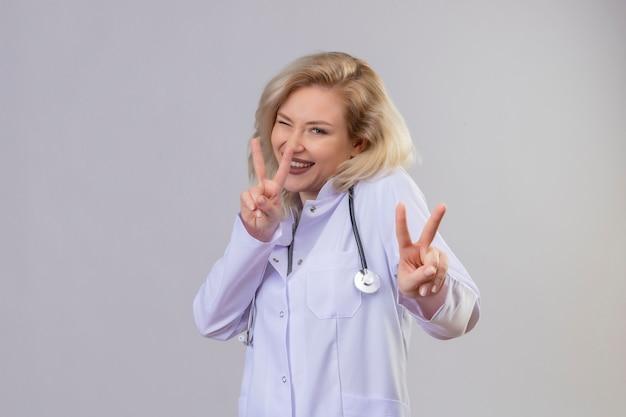 Glimlachende jonge arts die stethoscoop in medische toga draagt die vredesgebaar op witte muur toont