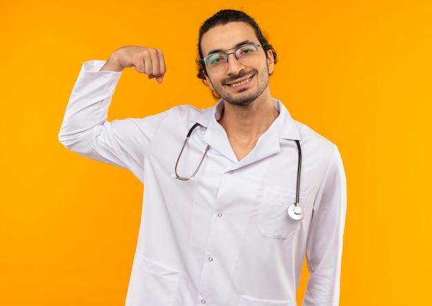 Glimlachende jonge arts met medische bril die medische gewaad met stethoscoop draagt die sterk gebaar op geel doet