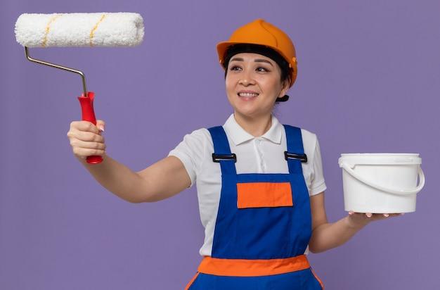 Glimlachende jonge aziatische bouwvrouw met oranje veiligheidshelm die naar verfroller kijkt en olieverf vasthoudt