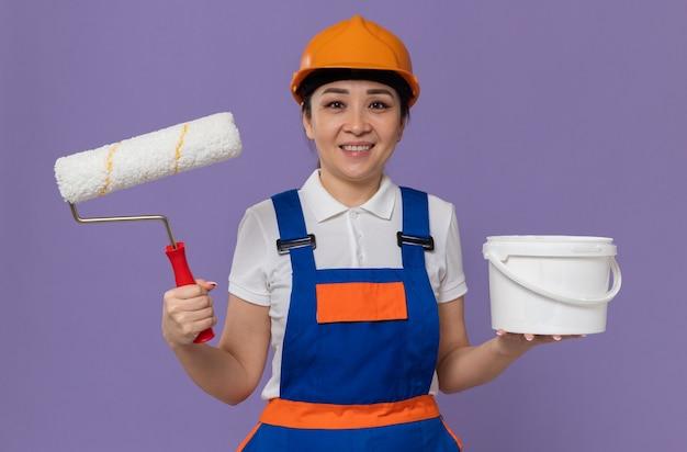 Glimlachende jonge aziatische bouwvrouw met oranje veiligheidshelm die verfroller en olieverf vasthoudt