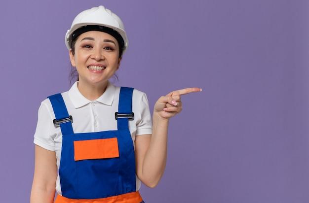 Glimlachende jonge aziatische bouwvrouw met witte veiligheidshelm die naar de zijkant wijst
