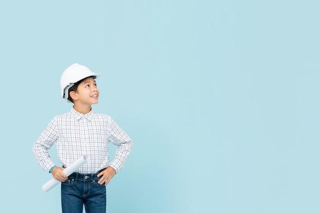 Glimlachende jonge aziatische jongen die toekomstige ingenieur willen zijn die witte bouwvakker en blauwdruk houden kijkend aan copyspace opzij