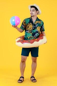 Glimlachende jonge aziatische man in gedrukt hawaiiaans shirt en zwemring op taille kijkt naar een kleurrijke strandbal. full body studio portret op gele achtergrond. zomer vakantie reizen voorbereiding concept.