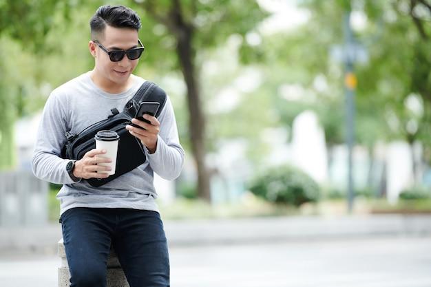 Glimlachende jonge aziatische man in zonnebril zittend op straatpaal en afhaalkoffiekopje vasthoudend terwijl hij sms't op de telefoon