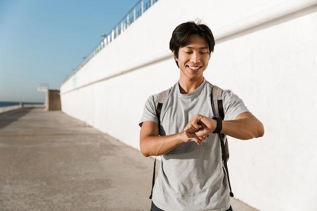 Glimlachende jonge aziatische man met een rugzak die tijd buitenshuis doorbrengt op het strand, de tijd controlerend