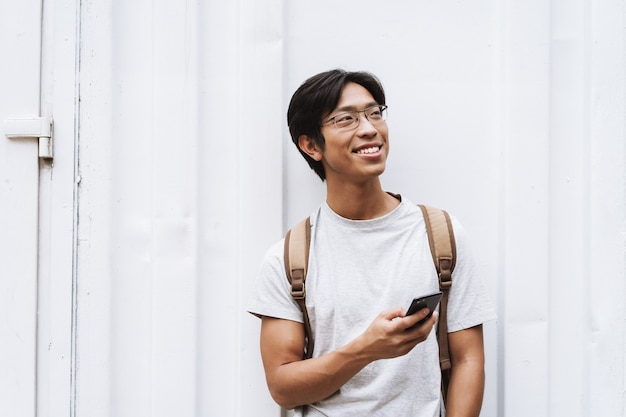 Glimlachende jonge aziatische man student met rugzak