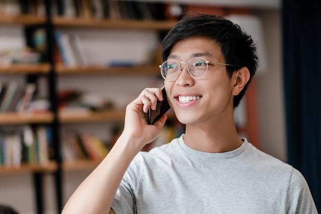 Glimlachende jonge aziatische mens in glazen die op de telefoon in het bedrijfbureau spreken