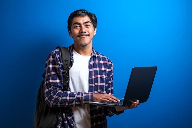 Glimlachende jonge aziatische student draagt shirt met moderne laptop tegen blauwe achtergrond met kopieerruimte.
