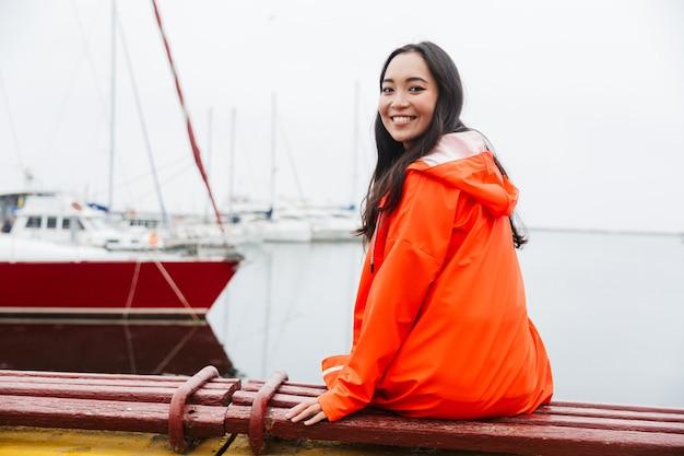Glimlachende jonge aziatische vrouw die een regenjas draagt die tijd buitenshuis doorbrengt met wandelen aan het kustland