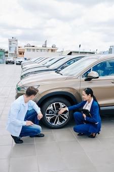 Glimlachende jonge aziatische vrouw die goede auto toont aan klant en de voordelen ervan uitlegt