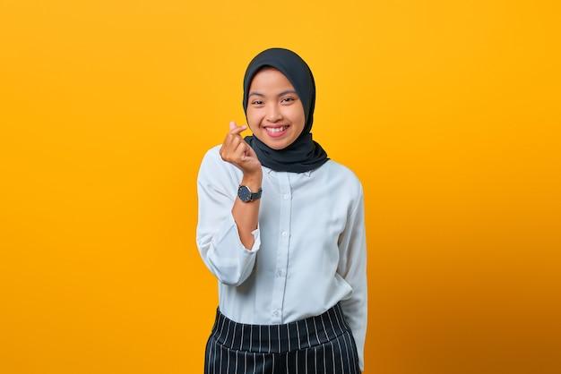 Glimlachende jonge aziatische vrouw die het teken van het liefdegebaar op gele achtergrond toont