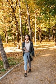 Glimlachende jonge aziatische vrouw die jas draagt die buiten in het park loopt, aan muziek met oortelefoons luistert, afhaalmaaltijdenkoffie houdt
