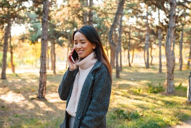 Glimlachende jonge aziatische vrouw die jas draagt die buiten in het park loopt, die op mobiele telefoon spreekt