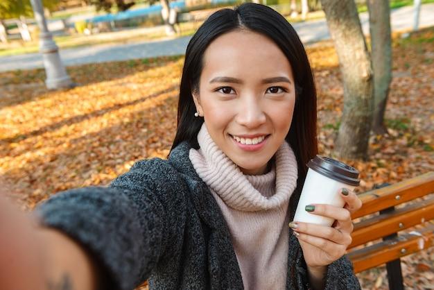 Glimlachende jonge aziatische vrouw die jas draagt die op een bankje in het park zit, een selfie neemt, koffiekop houdt