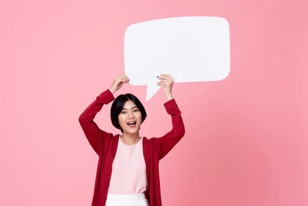 Glimlachende jonge aziatische vrouw die lege toespraakbel op roze achtergrond houdt