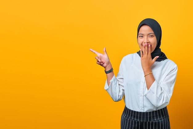 Glimlachende jonge aziatische vrouw die met de vingers naar de kopieerruimte wijst en naar de camera kijkt op een gele achtergrond